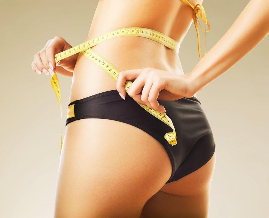slimming woman in panties with yellow measure